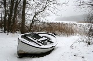 ruderboot im schnee vor schilf am see